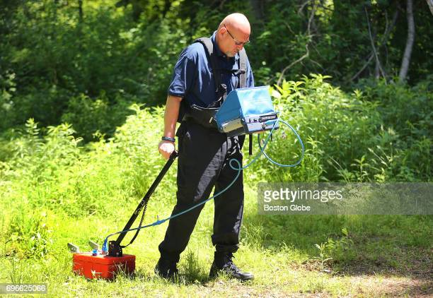 University of New Haven professor Peter Massey uses ground penetrating radar to search a former campground for a buried white car that might of been...