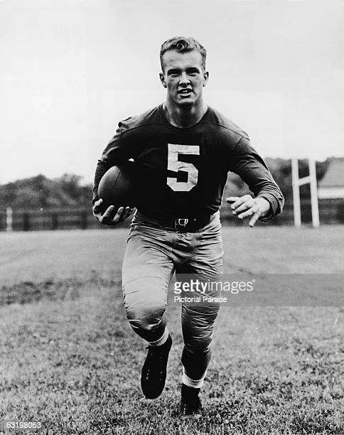 University of Notre Dame student Paul Hornung quarterback for the university's football team runs down a football field with the ball mid 1950s...