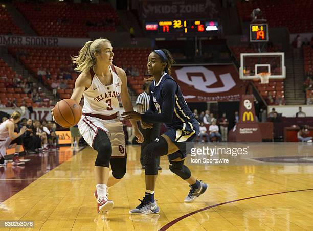 University of Oklahoma player Derica Wyatt dribbles the ball against Oral Roberts University [player Jordan Gilbert during the Oral Roberts...
