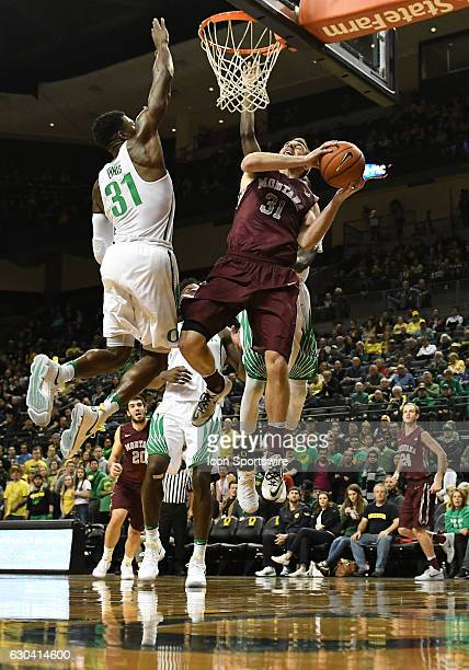 University of Oregon guard Dylan Ennis attempts to block the shot of University of Montana senior forward Jack Lopez during a nonconference NCAA...