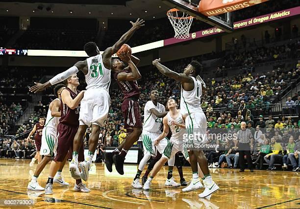 University of Oregon guard Dylan Ennis blocks the shot of University of Montana freshman guard Sayeed Pridgett during a nonconference NCAA basketball...