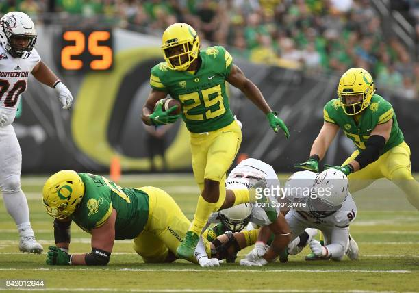 University of Oregon RB Kani Benoit breaks through the line on his way in for a second quarter touchdown during an NCAA football game between the...