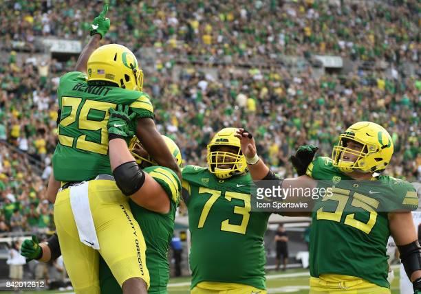 University of Oregon RB Kani Benoit celebrates with University of Oregon OL Tyrell Crosby and University of Oregon OL Jake Hanson on a 29yard run in...