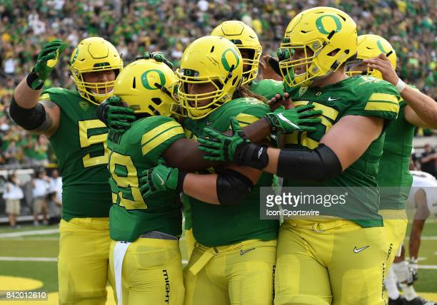 University of Oregon RB Kani Benoit is surrounded by his teammates after scoring his second touchdown of the first half during an NCAA football game...
