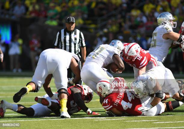 University of Oregon RB Royce Freeman runs the ball against University of Nebraska DL Mick Stoltenberg and University of Nebraska LB Luke Gifford...