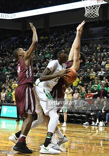 University of Oregon senior forward Chris Boucher attempts to shoot over University of Montana freshman guard Sayeed Pridgett and University of...