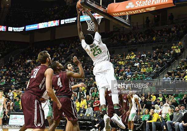 University of Oregon senior forward Chris Boucher slam dunks the ball over University of Montana freshman guard Sayeed Pridgett and University of...