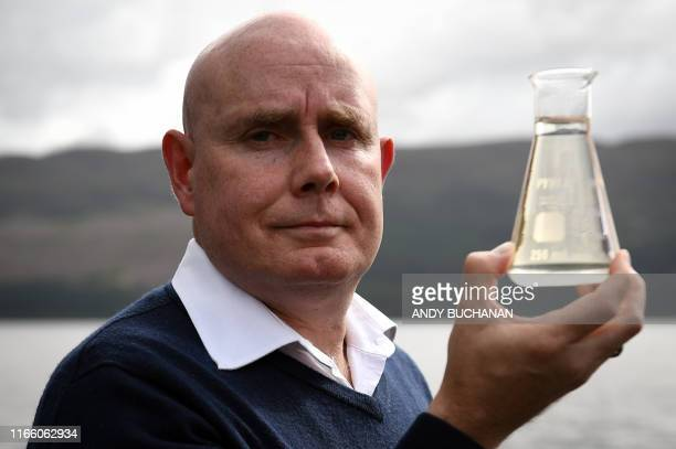 University of Otago geneticist Professor Neil Gemmell poses with a beaker of water on the shores of Loch Ness after announcing the results of...