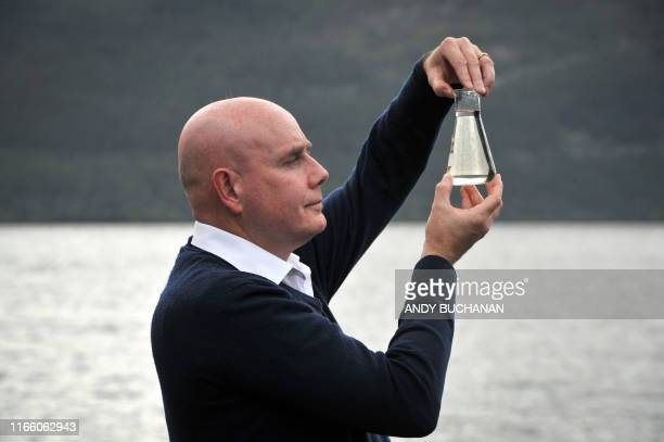 TOPSHOT University of Otago geneticist Professor Neil Gemmell poses with a beaker of water on the shores of Loch Ness after announcing the results of...