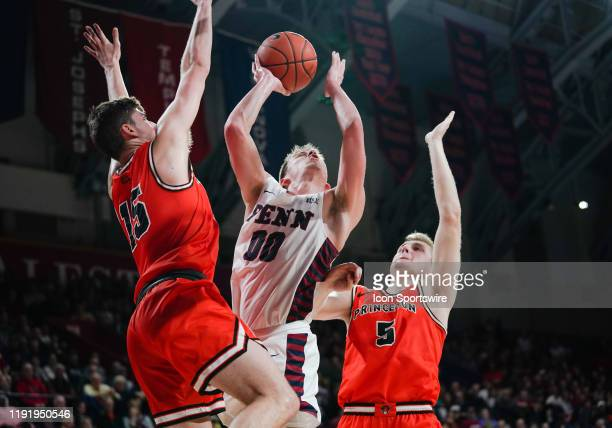 University of Pennsylvania Quaker guard Ryan Betley jumps for a layup between Princeton Tigers forward Drew Friberg and guard Ryan Schwieger during...