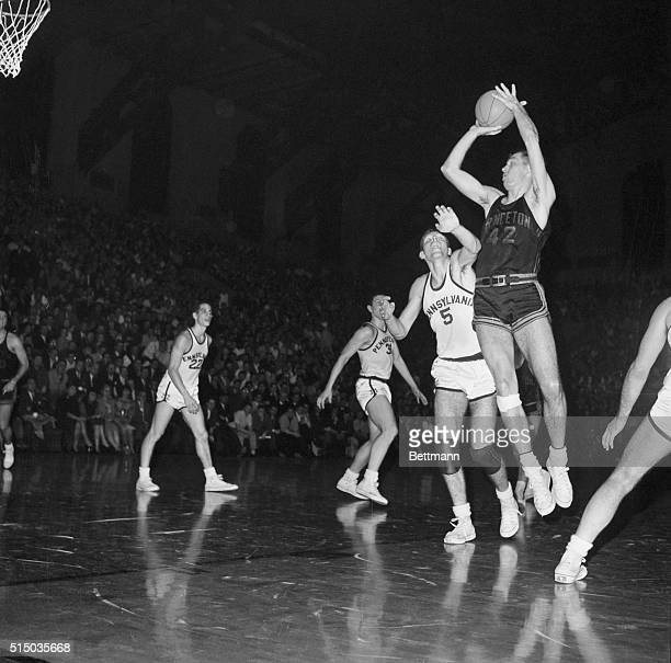 University of Pennsylvania senior letter man Bruce Moore makes a futile attempt to stop the basket shot of Princeton's court star Bill Bradley in the...