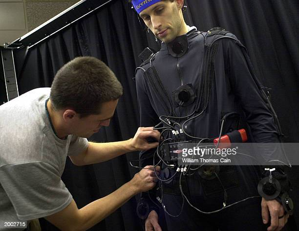 University of Pennsylvania student Aaron Bloomfield is connected to sensors by fellow student Durell Bouchard as they prepare to demonstrate the...