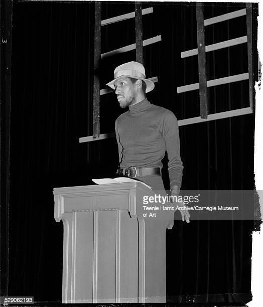 University of Pittsburgh professor Curtiss Porter wearing turtleneck and fedora speaking from podium at William Pitt Union Pittsburgh Pennsylvania...