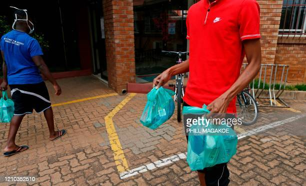 University of Pretoria's international students from Lesotho carry food parcels donated by Kindness Like Confetti a nongovernmental organisation in...