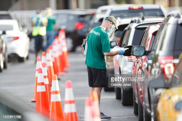 University of South Florida Health administrator talks to a driver before they receive a coronavirus test at the Lee Davis Community Resource Center...