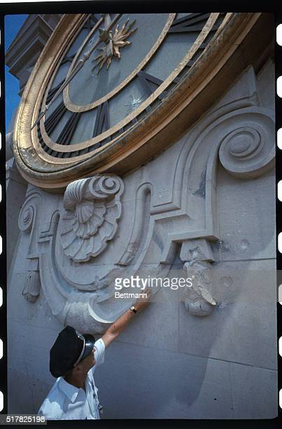 University of Texas policeman Earnest R Puryear points to bullet holes in tower building clock from which sniper Charles Whitman staged a wild...