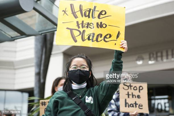 """University of Washington student who wished to remain anonymous holds a sign that reads """"hate has no place"""" during the We Are Not Silent rally..."""