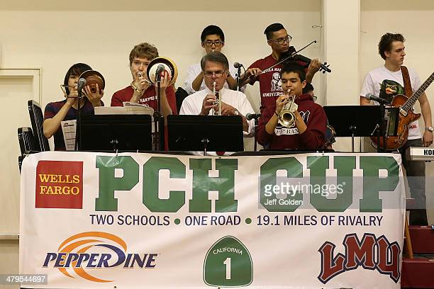 University President David Burcham plays the trumpet with Chris Delgado trombone players James Ho and Erik Anderson and the LMU Pep Band as they...