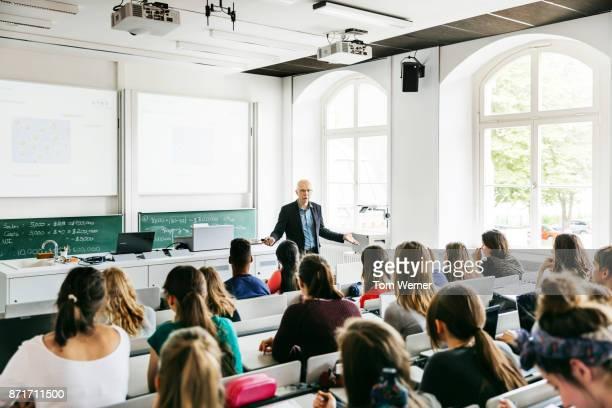 university professor addressing his pupils during lecture - hörsaal stock-fotos und bilder