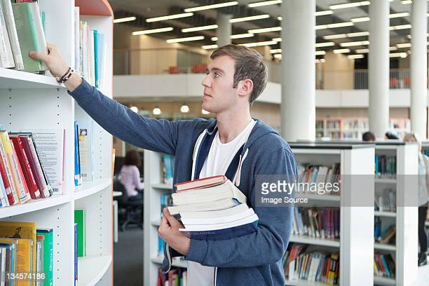 University student choosing textbooks in library