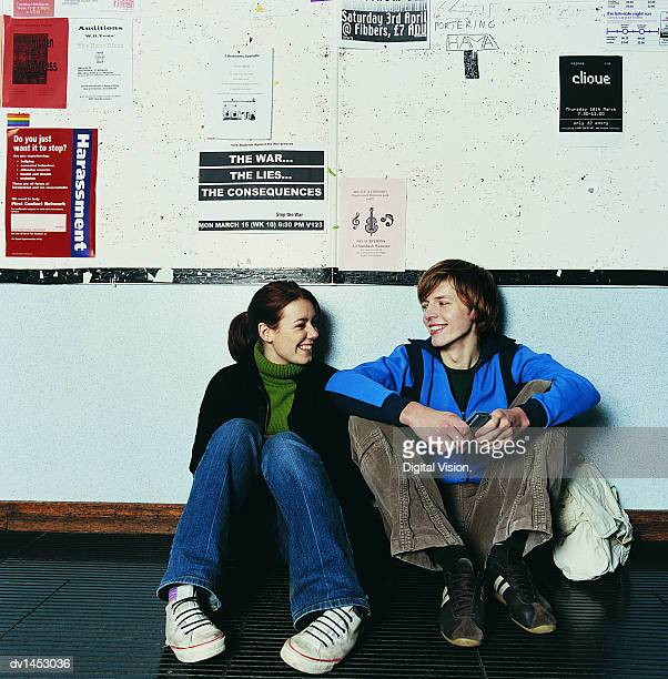 University Student Couple Sitting in a Corridor