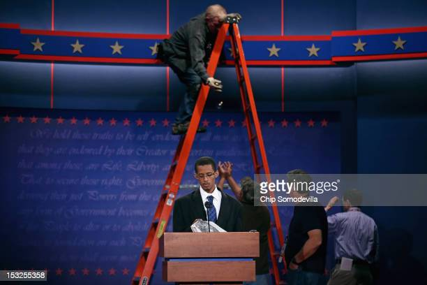 University student Dia Mohamed stands in for President Barack Obama as workers continue to prepare the stage for the first presidential debate in the...