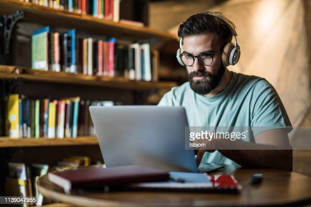 university student doing research. - online class stock pictures, royalty-free photos & images