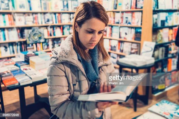 university student in the bookstore reading a book - book store stock photos and pictures