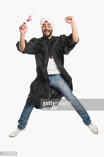 University student jumping with his graduation diploma