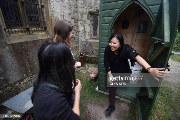 University student Kae Ono and her friends Andrea Stewart and Lingbo Zhou inspect the outside toilet at St Mary's Church, where guests can pay to...