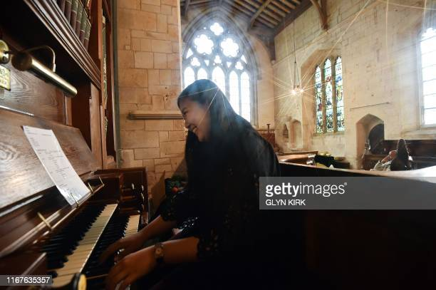 University student Kae Ono plays the church organ while her friends relax in the background at St Mary's Church where guests can pay to stay...