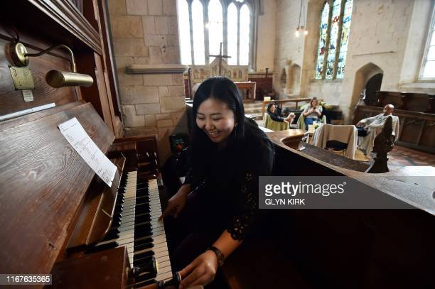University student Kae Ono plays the church organ while her friends relax in the background at St Mary's Church, where guests can pay to stay...