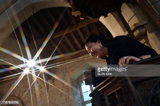 University student Kae Ono reads from the pulpit at St Mary's Church, where guests can pay to stay overnight in what is known as 'champing', in...