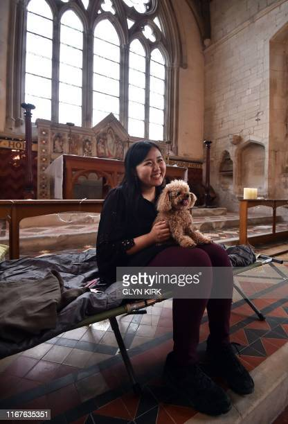 University student Kae Ono settles down with Coco the dog at St Mary's Church where guests can pay to stay overnight in what is known as 'champing'...