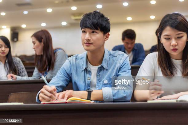 university student paying attention in class - college student stock pictures, royalty-free photos & images