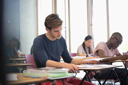 University student taking exam, students in background writing - gettyimageskorea