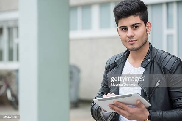 University student using digital tablet in campus School, Bavaria, Germany