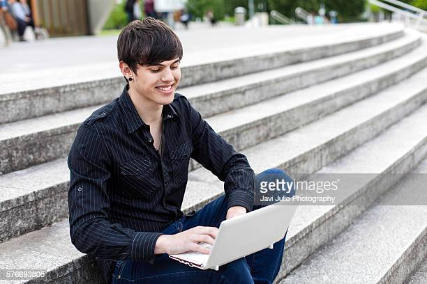 University student using laptop sitting on a stair