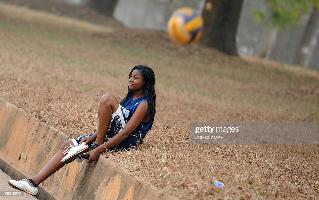 A university student watches her friends as they play volleyball next to the pitch where Sudan's football team takes their practice in Kumasi 25 January, 2008, during the African Cup of Nations football championship.
