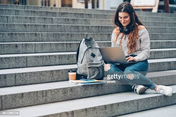 university student with laptop sitting outdoors - rucksack stock pictures, royalty-free photos & images