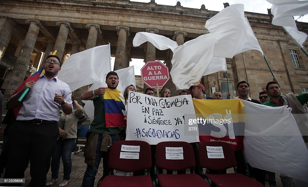 University students and supporters of the peace deal signed between the government and the Revolutionary Armed Forces of Colombia (FARC) rebels protest with a sign reading 'Stop War' in front of Congress in Bogota, Colombia, October 3, 2016. The Colombian government and FARC rebels scrambled Monday to save a peace deal after voters narrowly rejected it in a referendum, throwing the four-year-old peace process into uncertainty. / AFP / STR