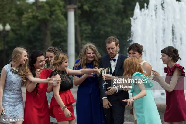 University students celebrate graduation day as a rehearsal of a flypast goes overhead on June 30 2017 in Minsk Belarus Independence Day also known...