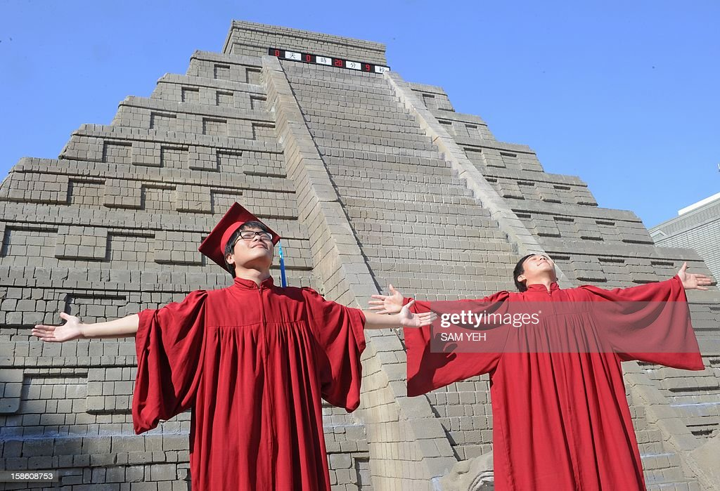 University students celebrate their gradulation in front of a replica of a Mayan pyramid before a count-down ceremony organized by the National Museum of Natural Science to help ensure the public it is not the end of the world, in central Taichung on December 21, 2012. A digital 'doomsday clock' on top of a two-storey replica Mayan pyramid erected at a museum in central Taiwan's Taichung city completed its countdown for the end of the world at 0600 GMT -- midnight in Mexico. AFP PHOTO / Sam Yeh