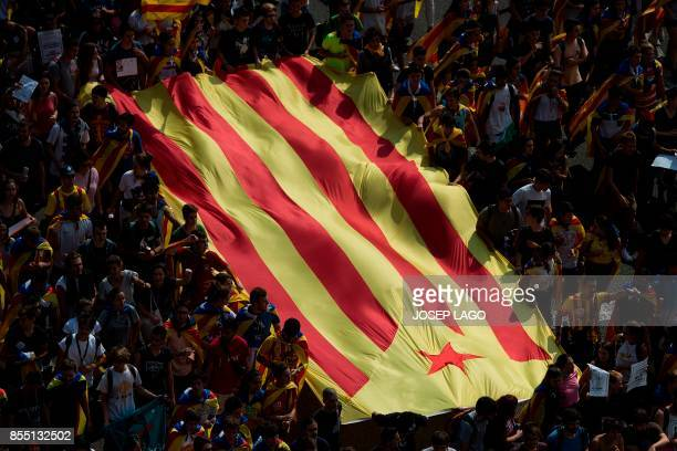 TOPSHOT University students hold Catalan proindependence 'Estelada' flag during a demonstration against the position of the Spanish government on the...