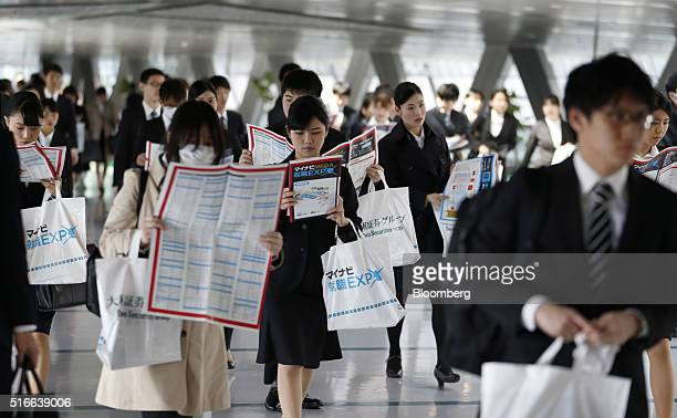 University students hold floor maps as they walk through a job fair hosted by Mynavi Corp in Tokyo Japan on Sunday March 20 2016 The Bank of Japan...