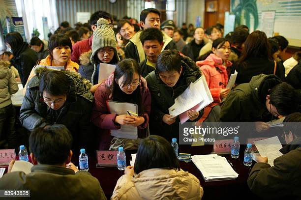 University students line up to hand in their resumes at a job fair of nationwide meteorological departments for graduating students on December 7...