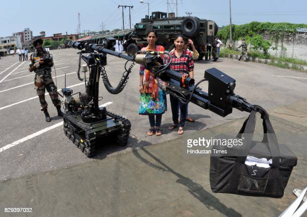 University students look at the instruments and weapons used by the Indian Army during an exhibition at Jammu University on August 10 2017 in Jammu...