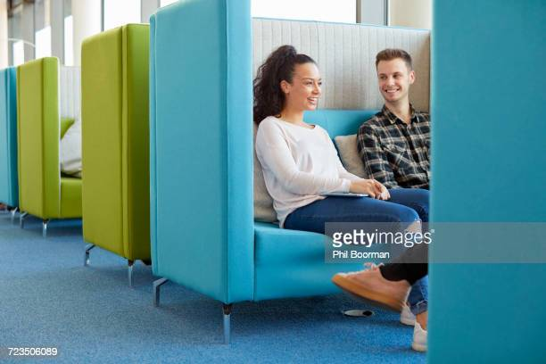 University students relaxing in modern cubicle seating area