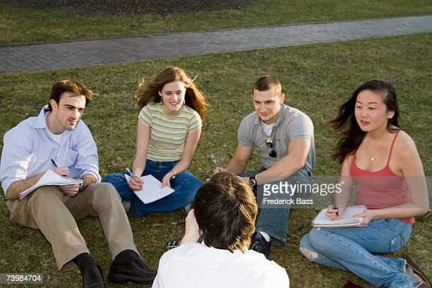 University students sitting on grass with lecturer