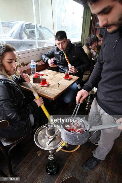 University students smoke the hookah or the water pipe in a cafe in downtown Ankara on January 31 2013 After banning smoking in public places the...